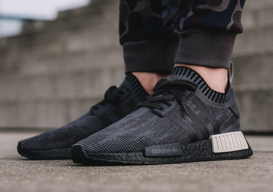 "The adidas NMD R1 Primeknit ""Pitch Black"" Adds Tan Heel Bumpers"